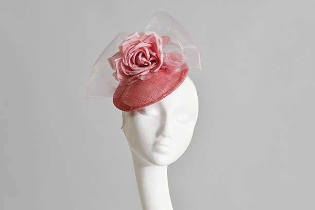 Candy Pink button Hat with silk flower and crinoline bow sited on front left of models head and model looking to camera while facing to the right