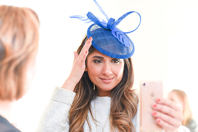 Royal blue fascinator face on with model touching it with her right hand and admiring it on her mobile phone front facing to camera, feathers and round base perching on left of models forehead with ribbon loops for height.