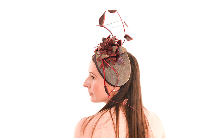 Glimmering Wine Percher is a beautiful classic vintage style cocktail hat with added height of feather vine and leather flower, hand made and wired on a buckram base covered with a fantastic sparkle fabric that is both silver or gold in different light. Model is staring off to the left and left shoulder towards the camera