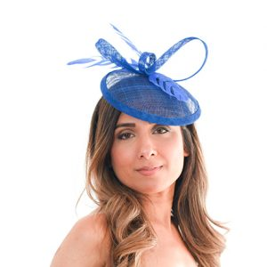 Royal blue fascinator face on with model front facing to camera, feathers and round base perching on left of models forehead with ribbon loops for height.