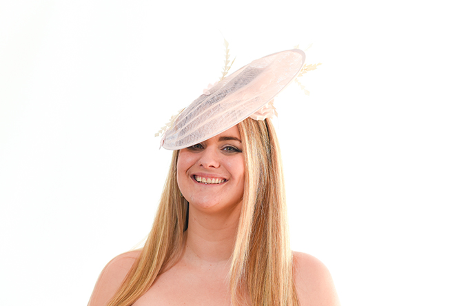 Light Pink Hatinator with underside silk flower visible on the smiling model to the camera