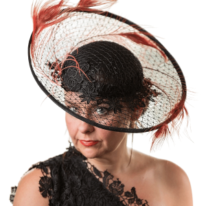 Model looking face on with hat in full, Model looking through transparent brim and wearing black lace one shoulder dress.